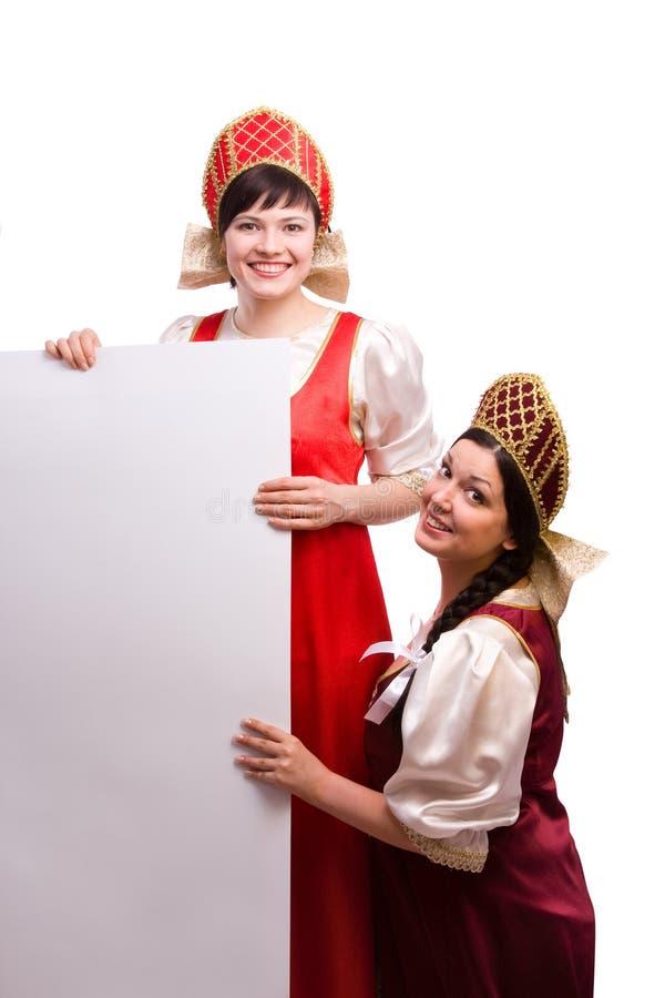 Femmes dans le costume russe avec le panneau-réclame. photo libre de droits
