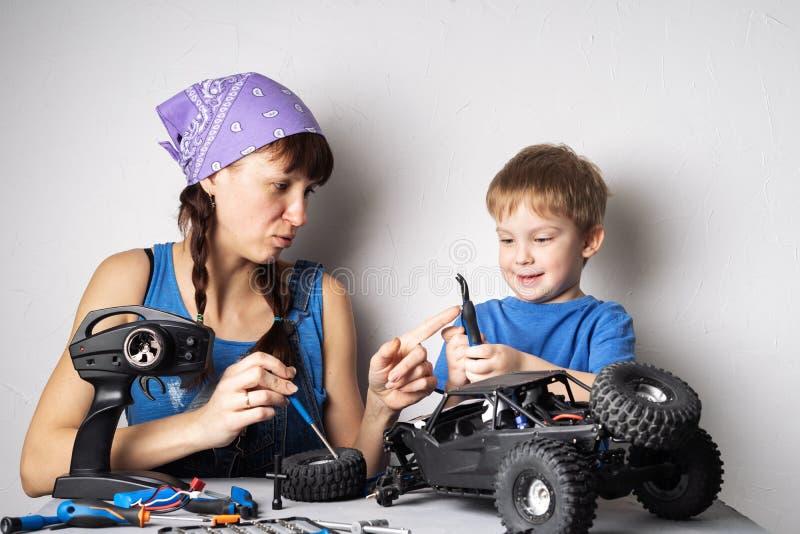 Femmes dans le travail des hommes : La maman aide son fils avec la fixation un modèle avec des erreurs radioguidé image stock