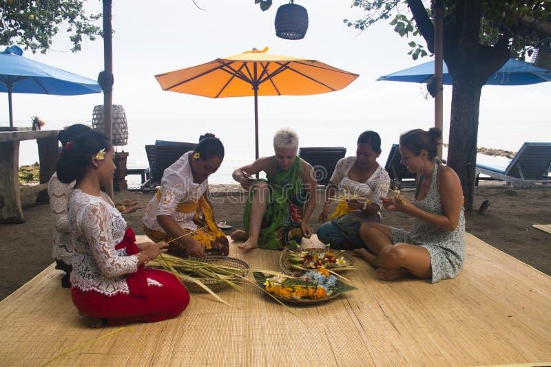 Femmes de Balinese faisant des offres à partir des fleurs images libres de droits