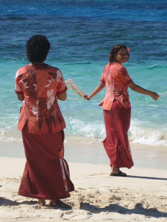 Femmes de Fijian souhaitant la bienvenue à des touristes avec des programmes photographie stock libre de droits