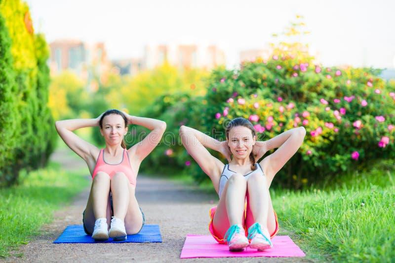Femmes de forme physique de sport formant des pousées L'exercice d'athlète féminin enfoncent dehors le parc vide Modèle convenabl images libres de droits