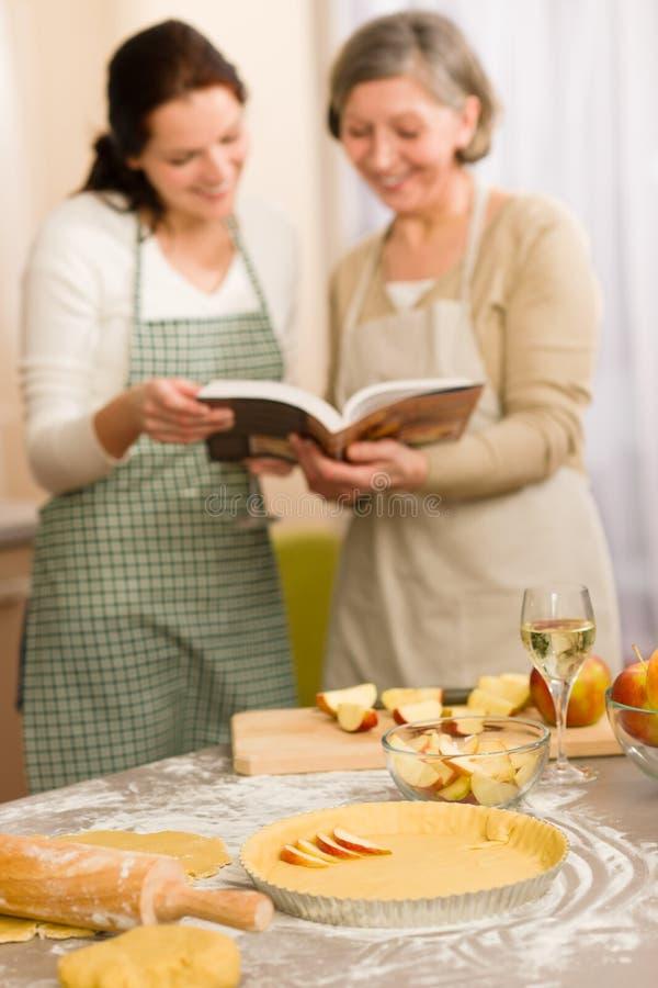 Femmes de la recette deux de secteur d'Apple regardant le livre de cuisine image stock