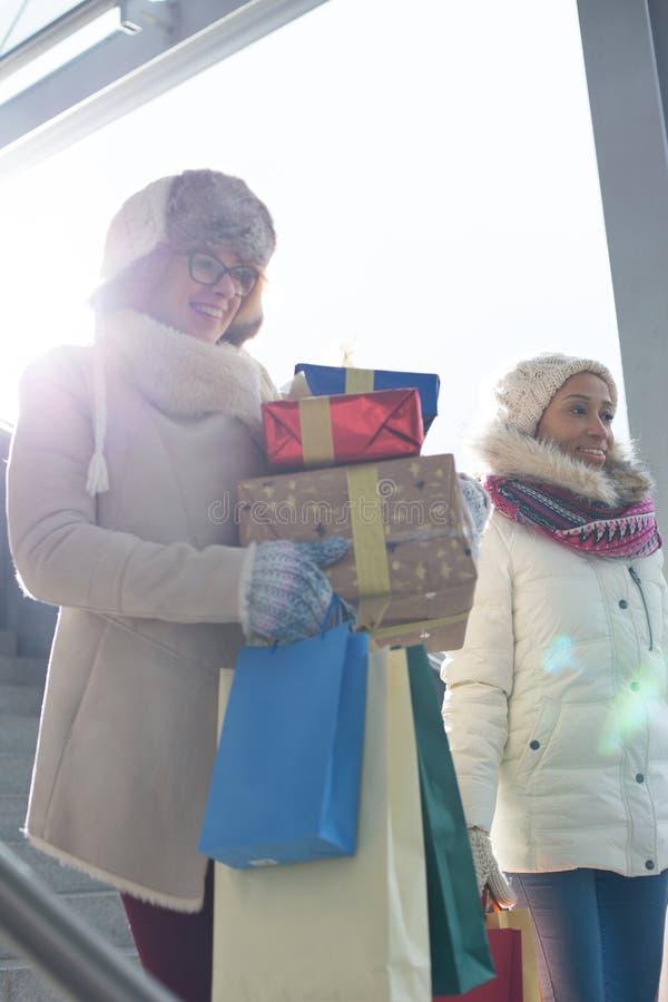 Femmes de sourire avec des cadeaux et des paniers par la fenêtre pendant l'hiver photographie stock