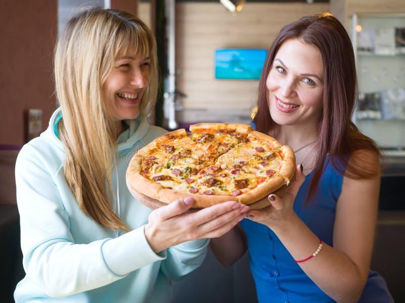 Femmes de sourire blanches avec la pizza à disposition en café images libres de droits