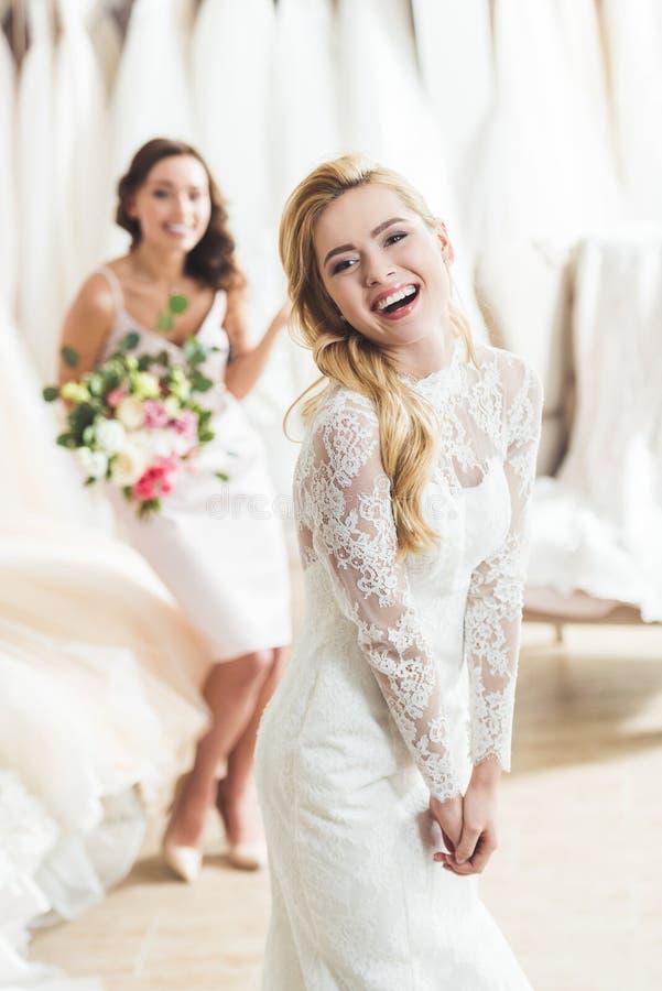 Femmes de sourire dans des robes de mariage avec des fleurs image libre de droits