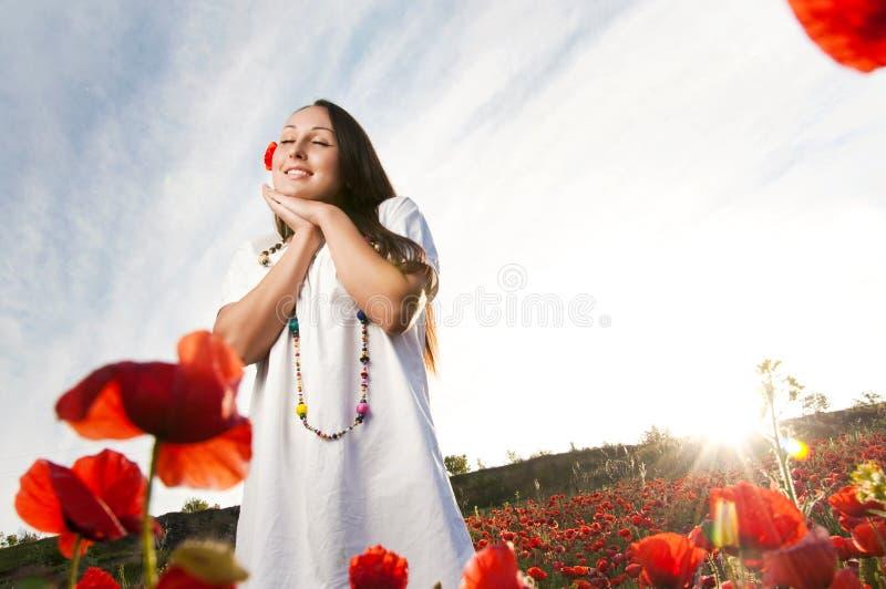 Femmes de sourire dans un domaine de pavot images libres de droits