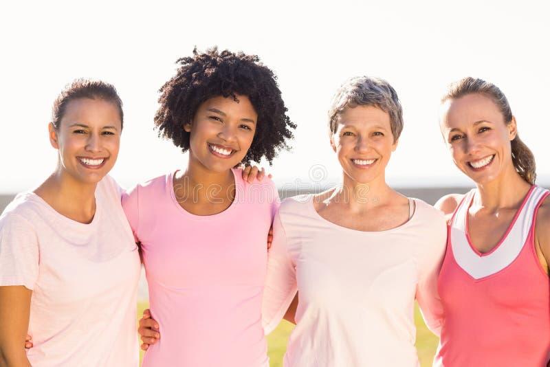 Femmes de sourire portant le rose pour le cancer du sein image stock