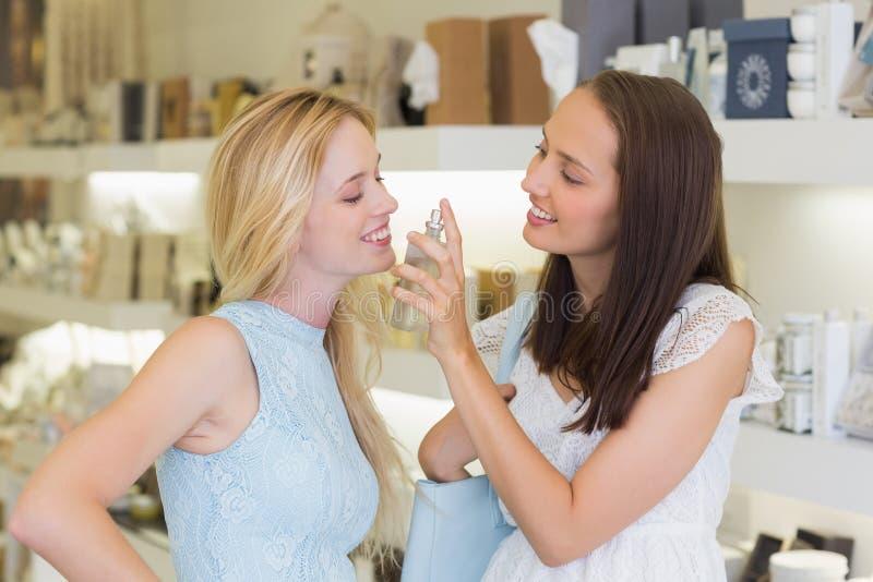 Download Femmes De Sourire Pulvérisant Le Parfum Image stock - Image du people, mail: 56490911