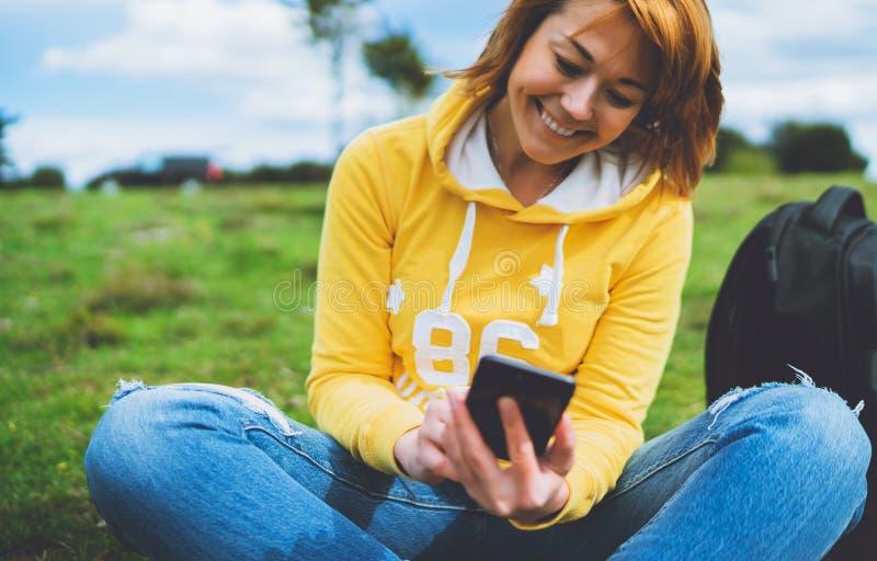 Femmes de sourire se tenant en technologie femelle d'instrument de mains, jeune fille de touristes sur l'herbe verte de fond util images libres de droits