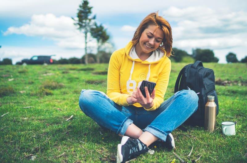 Femmes de sourire se tenant en technologie femelle d'instrument de mains, jeune fille de touristes sur l'herbe verte de fond util images stock
