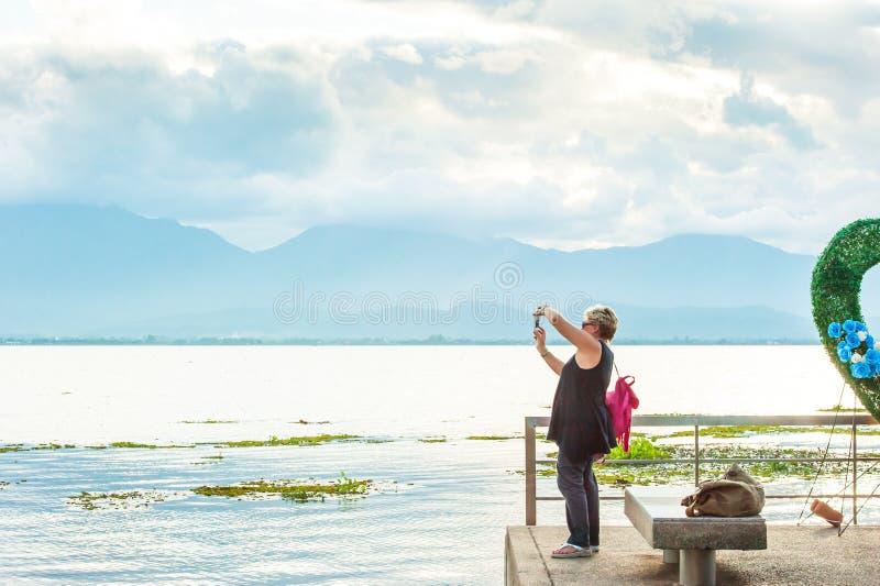 Femmes de touristes de détente se tenant sur la terrasse au bord de lac et à apprécier la vue de lac avec la caméra, coucher du s photo libre de droits