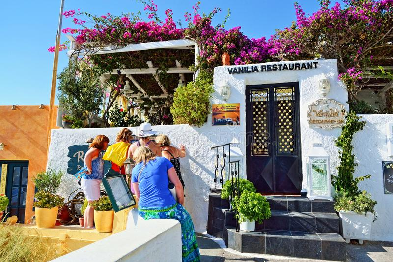 Femmes de touristes explorant le menu Santorini de restaurant photos stock