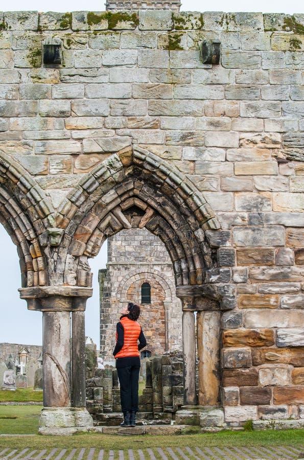 Femmes de touristes observant les ruines de Saint Andrews photo stock