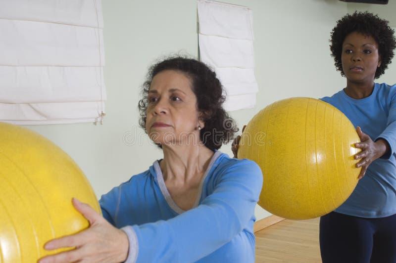 Femmes employant des boules d'exercice dans la classe de forme physique photos libres de droits