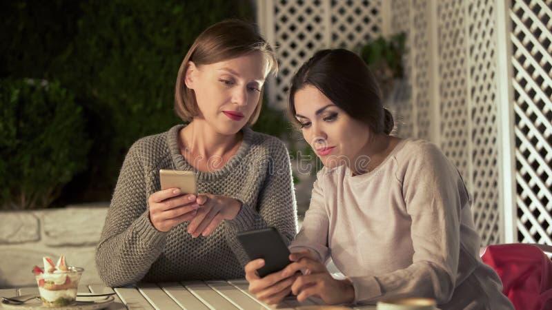 Femmes employant l'appli mobile se reposant en café, achats en ligne, causerie sociale de réseaux photos libres de droits