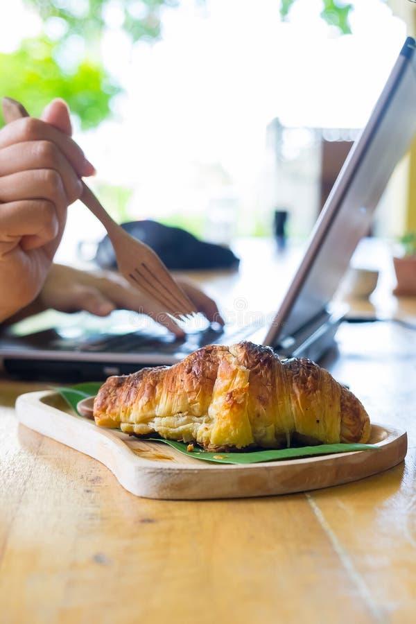 Femmes employant une fourchette pour manger des croissants et à l'aide de l'ordinateur portable photo stock