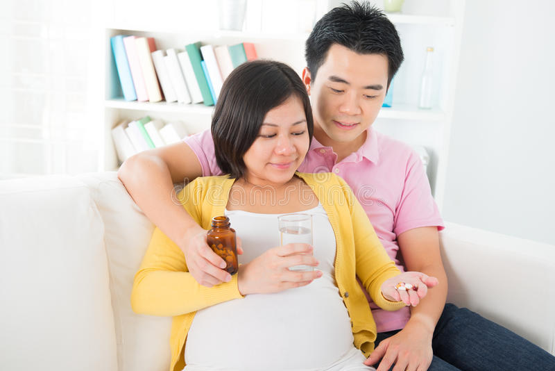 Femme enceinte d'Asiatique ayant la médecine à la maison photographie stock