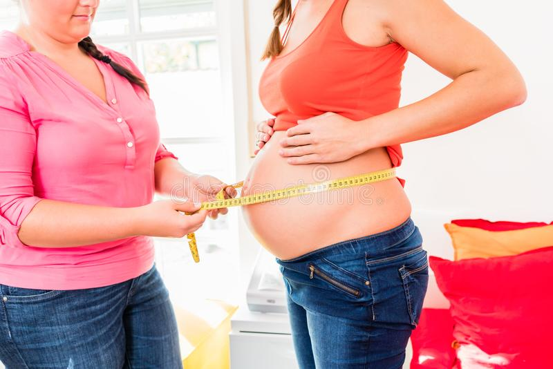 Femmes enceintes debout et circonférence de mesure de sage-femme de b photo stock