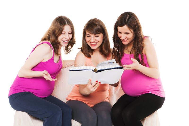 Femmes enceintes heureuses de sourire reposant et lisant a image libre de droits