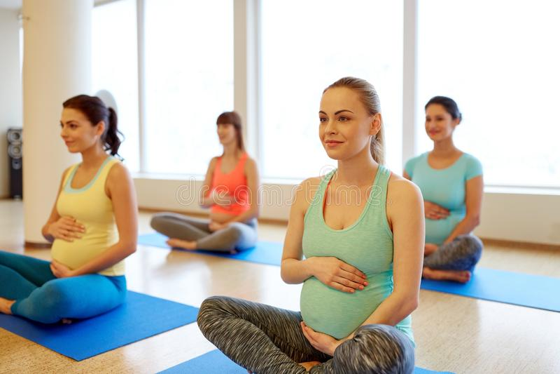 Femmes enceintes heureuses s'exer?ant au yoga de gymnase photo stock