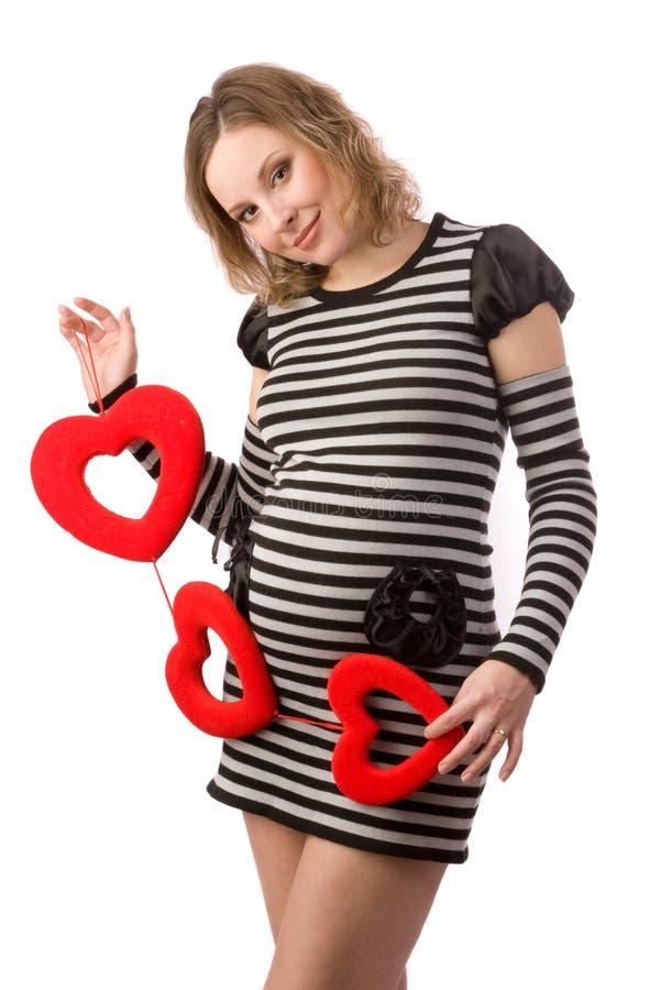 Femmes enceintes retenant les coeurs affichés image stock