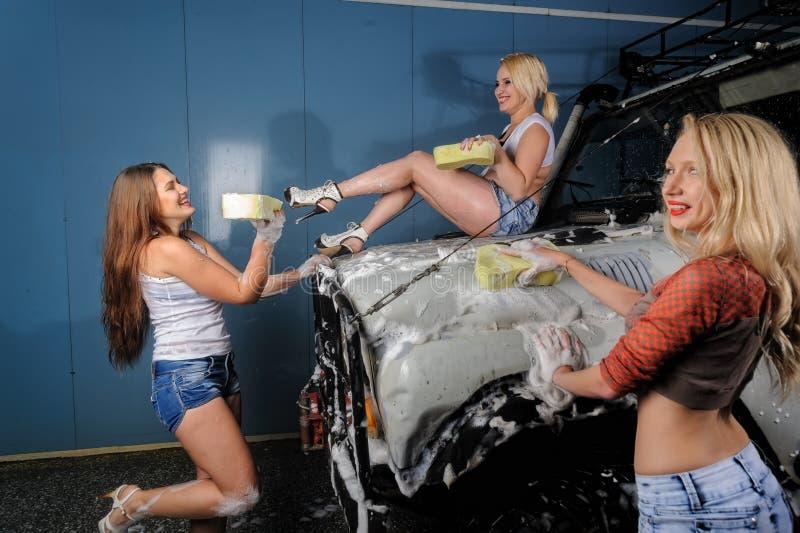 Femmes espiègles sexy lavant la voiture avec l'amusement photo libre de droits