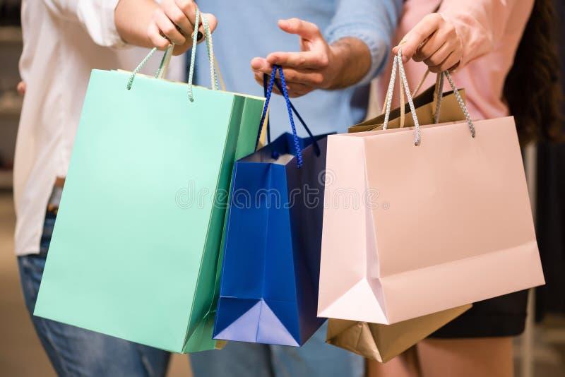 Femmes et homme avec les sacs à provisions de papier, plan rapproché photos libres de droits
