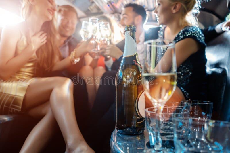 Femmes et hommes c?l?brant avec des boissons dans une voiture de limousine photo stock