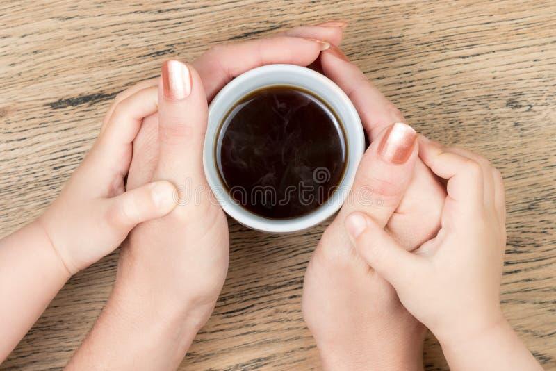 Femmes et mains d'enfant tenant le café photos stock