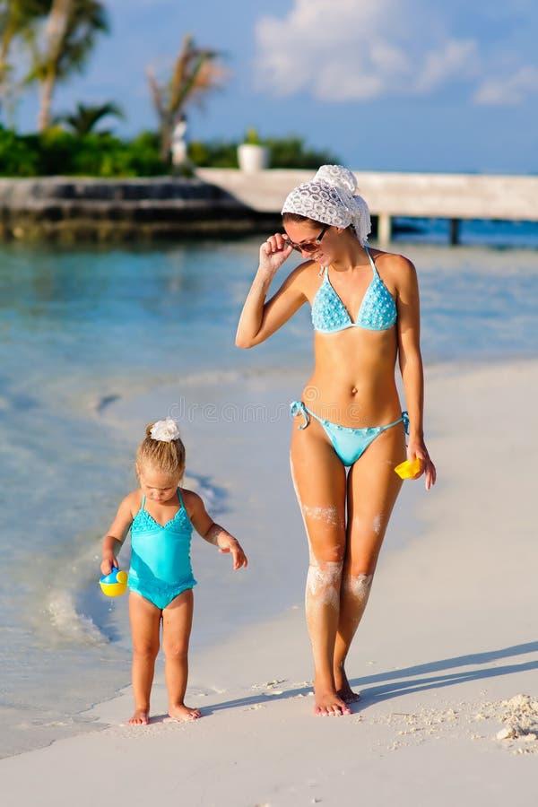 Femmes et son descendant marchant sur la plage tropicale images stock