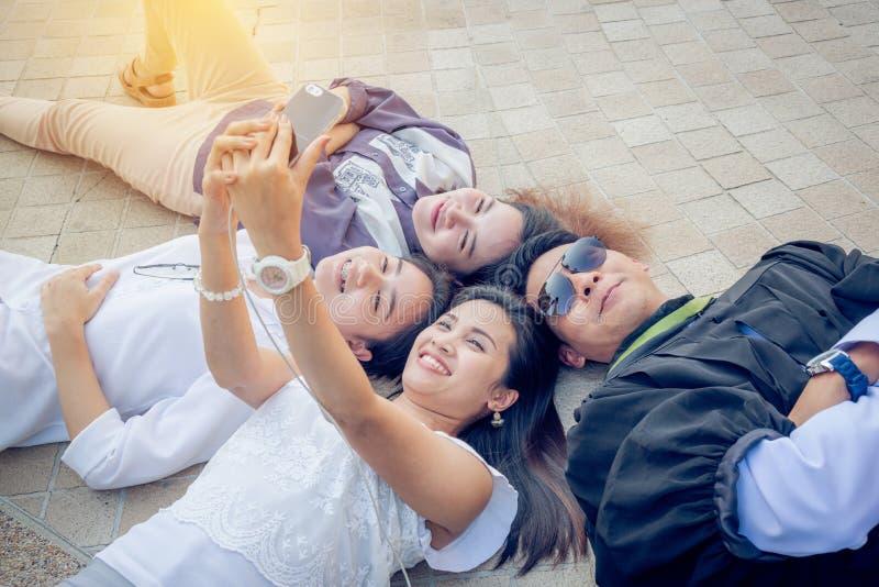 Femmes et un homme prenant leur photo par le téléphone portable images libres de droits