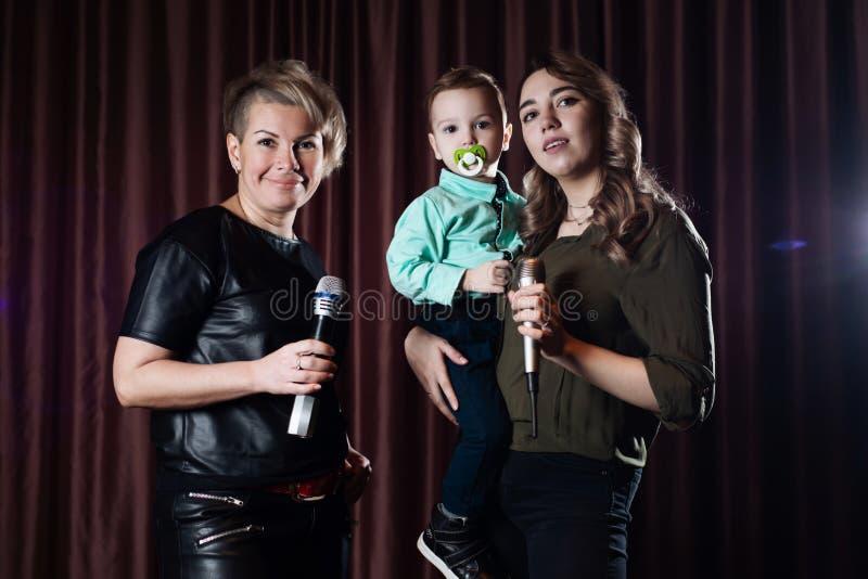Femmes et un petit enfant chanter sur l'étape dans des microphones dans le karaoke sur un fond des rideaux rouges photos libres de droits