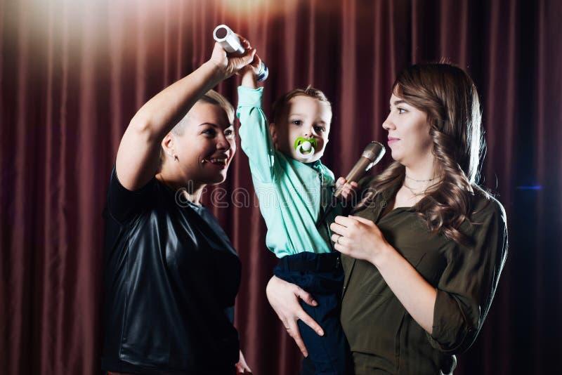 Femmes et un petit enfant chanter sur l'étape dans des microphones dans le karaoke sur un fond des rideaux rouges images libres de droits