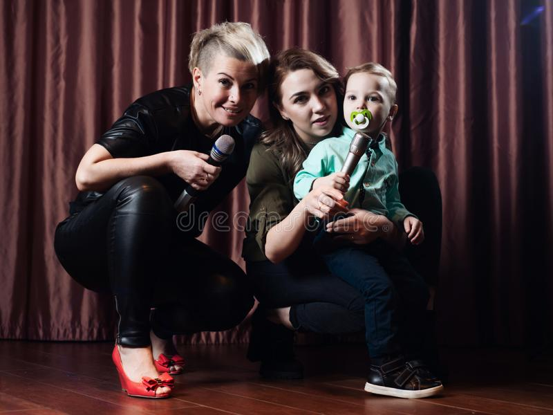Femmes et un petit enfant chanter sur l'étape dans des microphones dans le karaoke sur un fond des rideaux rouges images stock
