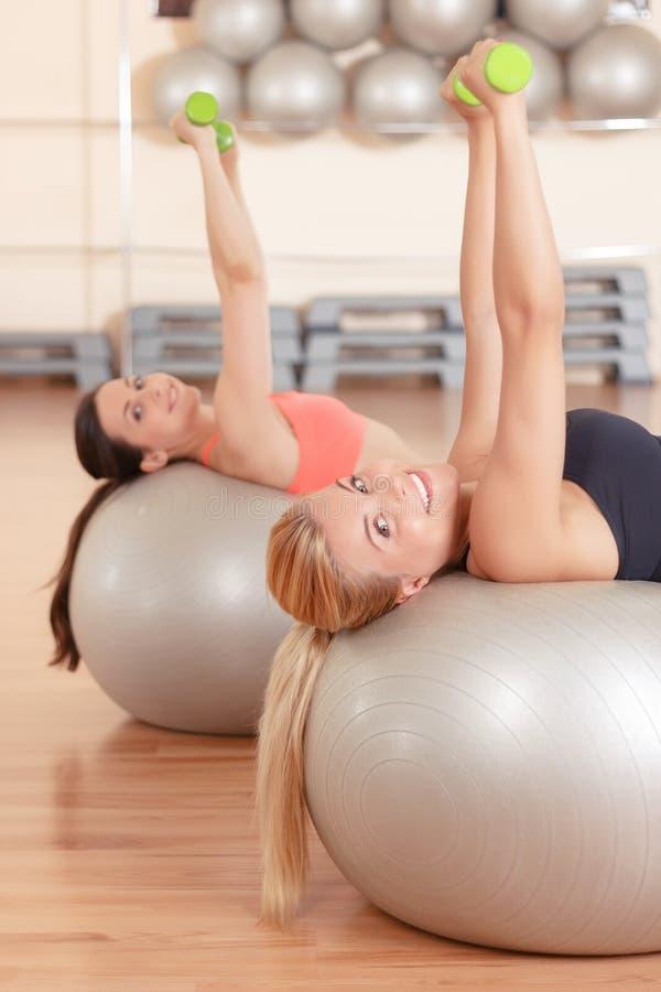 Femmes faisant la forme physique de poids sur des boules photographie stock