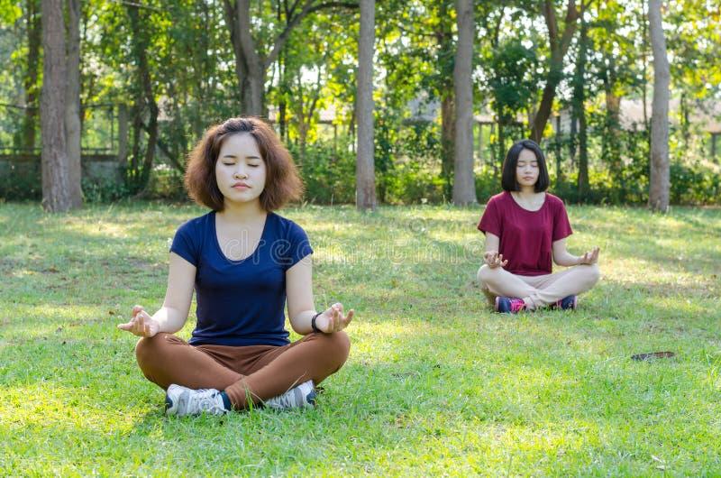 Femmes faisant le yoga en parc image stock