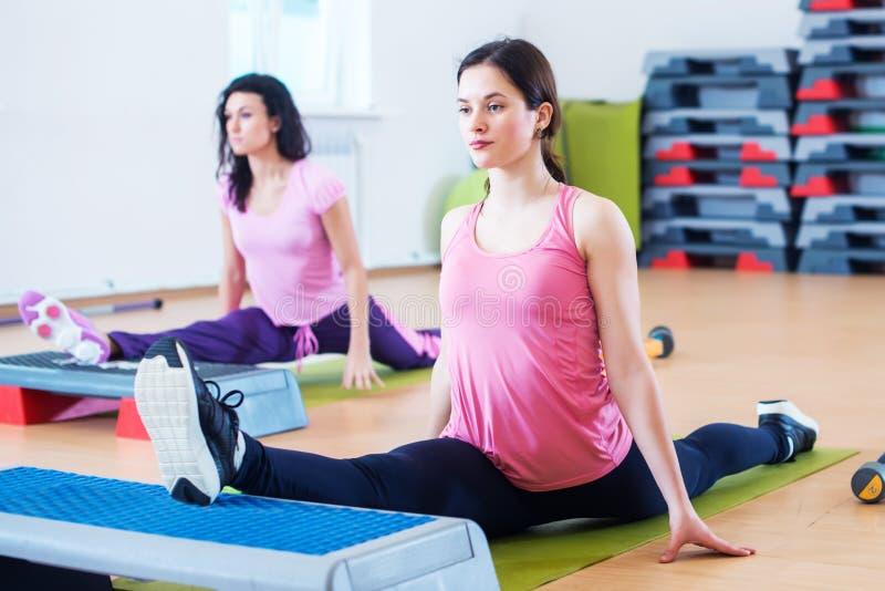 Femmes flexibles d'ajustement étirant des jambes avec les plates-formes aérobies d'étape photographie stock libre de droits