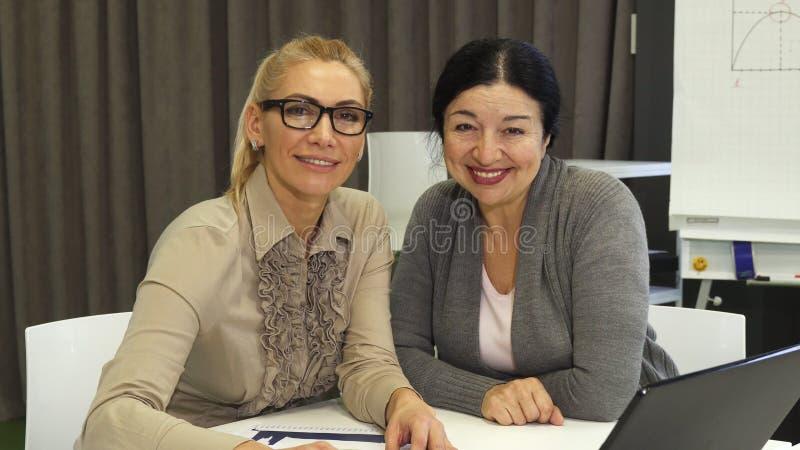 Femmes gaies d'affaires souriant à l'appareil-photo tout en travaillant sur l'ordinateur portable photographie stock