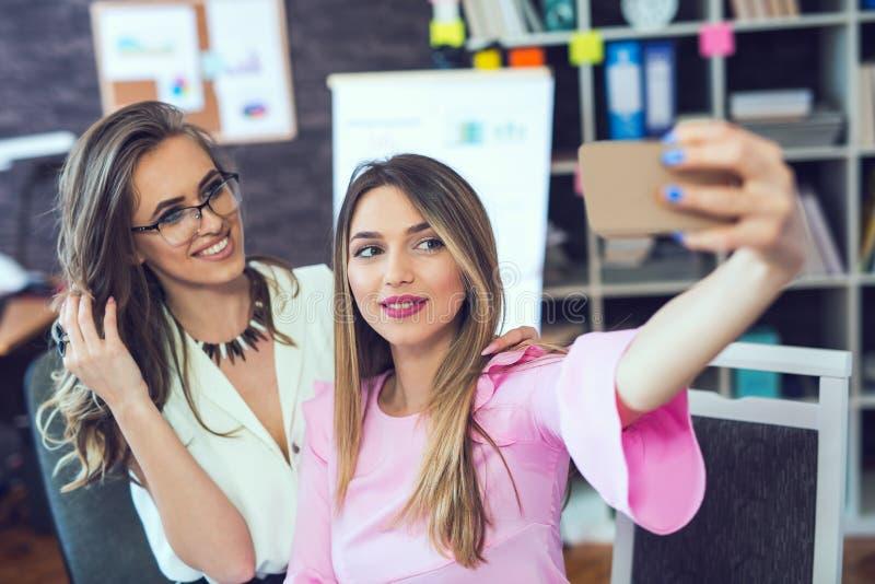 Femmes gaies de sourire d'affaires prenant un selfie images stock