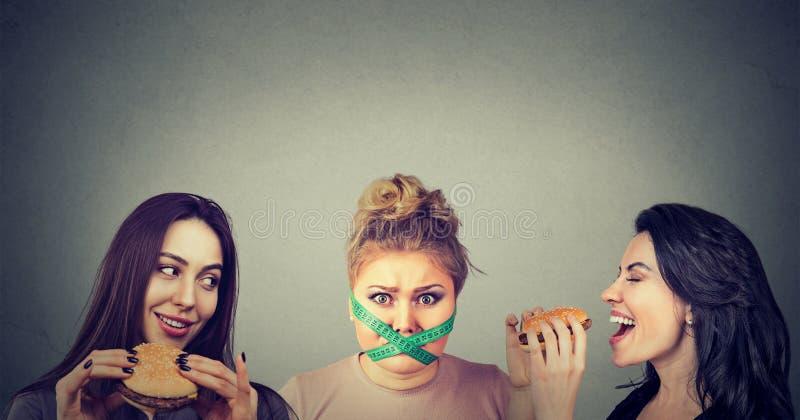 Femmes grosses et minces avec les aliments de préparation rapide photo stock