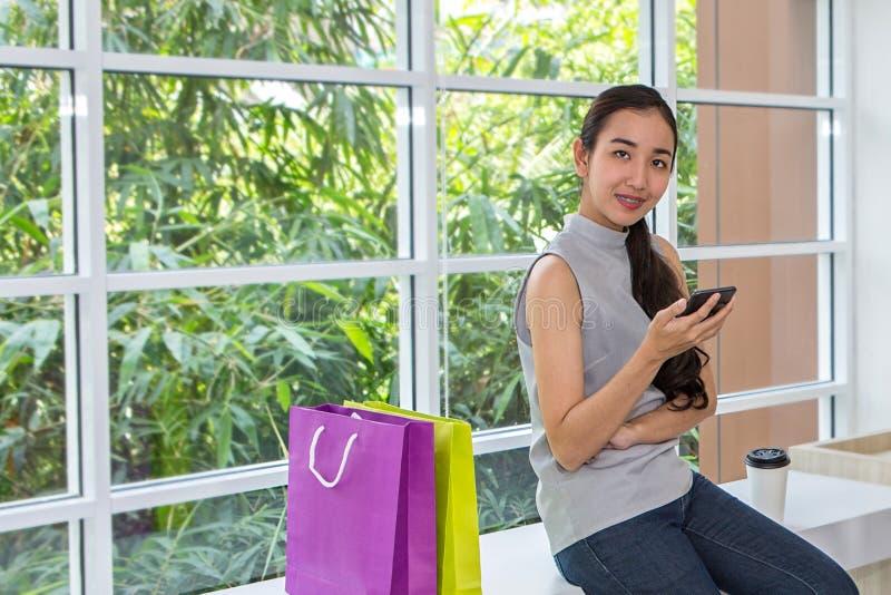 Femmes heureuses à l'aide du téléphone portable et du comprimé se reposant dans le café Travail femelle avec le comprimé utilisan photos stock