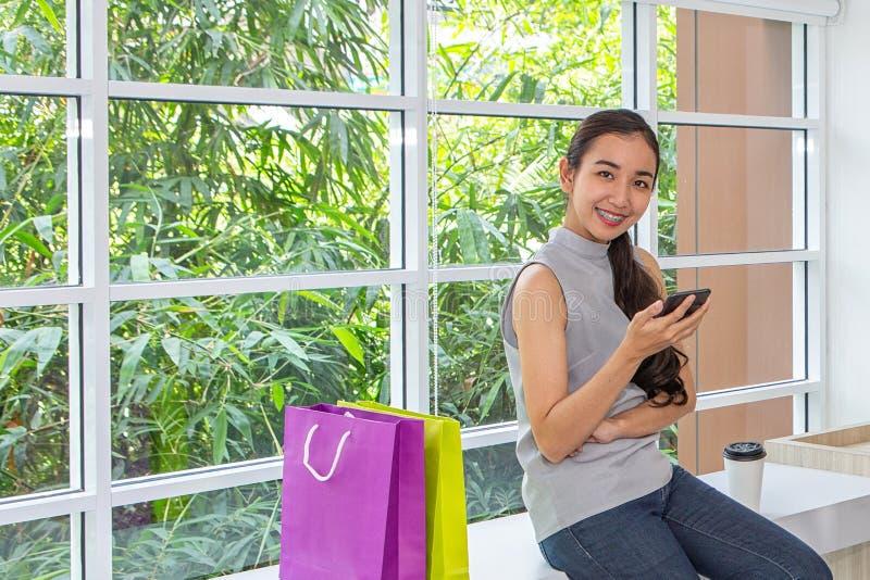 Femmes heureuses à l'aide du téléphone portable et du comprimé se reposant dans le café Travail femelle avec le comprimé utilisan images libres de droits