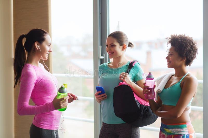 Femmes heureuses avec des bouteilles de l'eau dans le gymnase image libre de droits