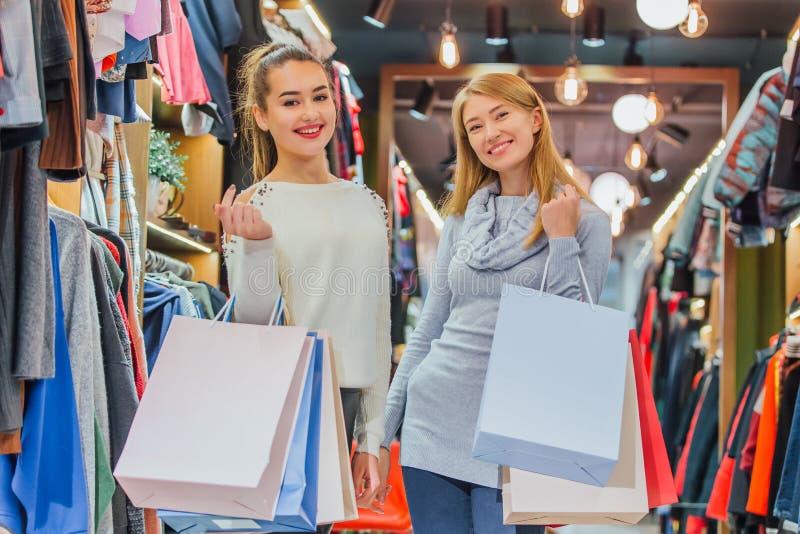 Femmes heureuses avec des sacs à provisions dans le magasin photos stock