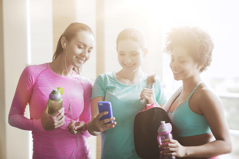 Femmes heureuses avec les bouteilles et le smartphone dans le gymnase photographie stock libre de droits