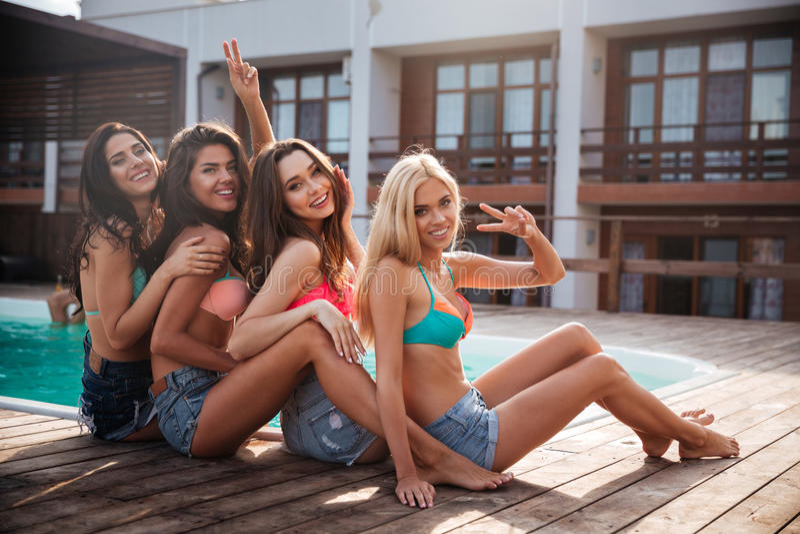 Femmes heureuses détendant et ayant l'amusement ensemble près de la piscine photo libre de droits