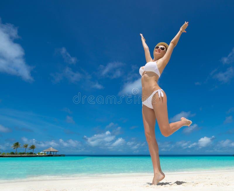 Femmes heureuses dans le bikini sur la plage tropicale images stock