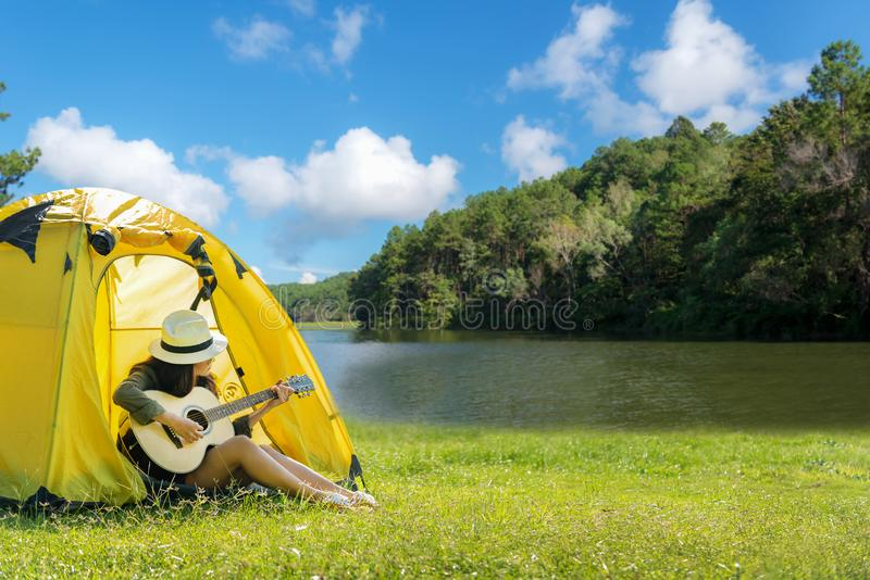 Femmes heureuses de voyageur sur le camping de vacances avec des tentes jouant la guitare dans la forêt près de la rivière image libre de droits