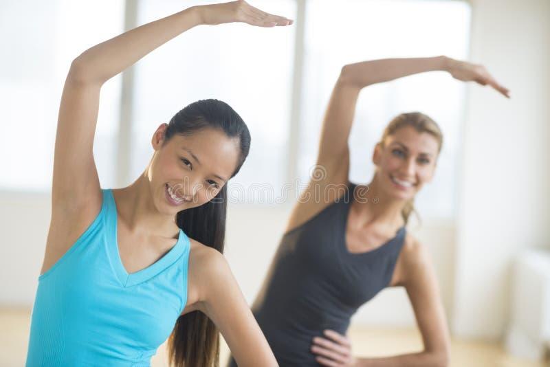 Femmes heureuses faisant étirant l'exercice au gymnase image libre de droits