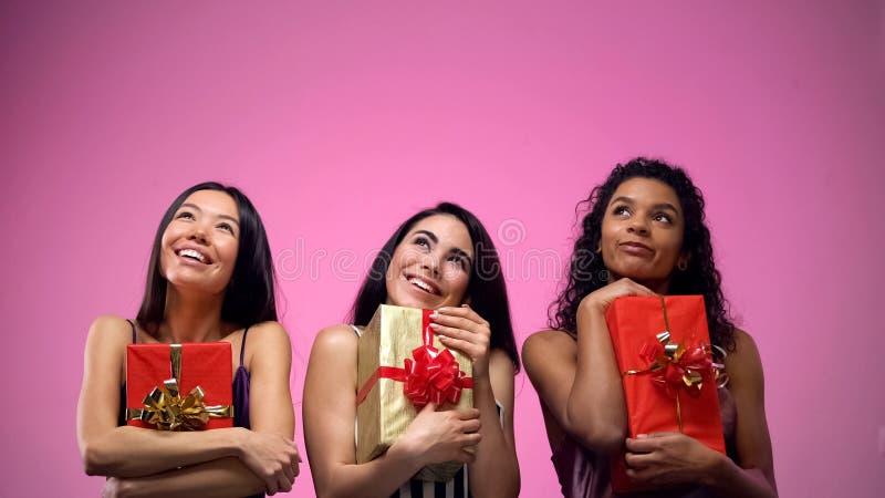 Femmes heureuses tenant des pr?sents et recherchant, publicit? de boutique de cadeaux, calibre photographie stock libre de droits